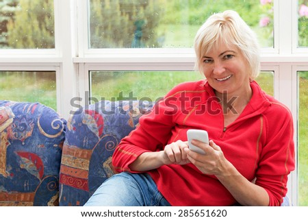 Smiling blonde middle-aged woman is sitting on a sofa and is looking to the camera. She is holding a white cell phone in her hands. All potential trademarks are removed. - stock photo