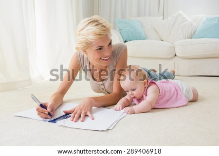 Smiling blonde mother with her baby girl writting on a copybook at home in the living room - stock photo