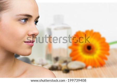 Smiling blonde natural beauty against beauty products with flower and pebbles - stock photo