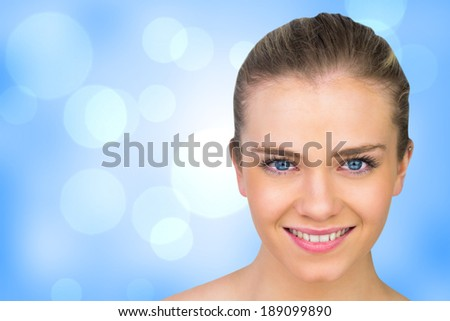 Smiling blonde natural beauty against blue abstract light spot design - stock photo