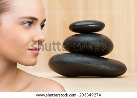Smiling blonde natural beauty against stack of smooth balancing rocks - stock photo
