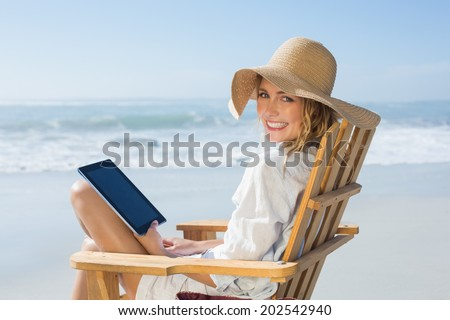 Smiling blonde sitting on wooden deck chair by the sea using tablet on a sunny day - stock photo