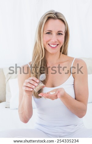 Smiling blonde taking her pills at home in the bedroom