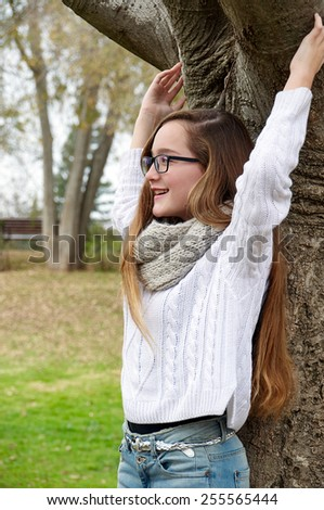 Smiling blonde teenager girl in the spring park - stock photo