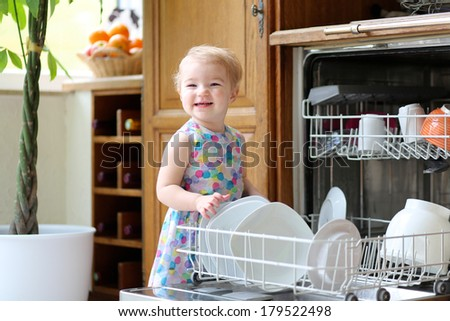 Smiling blonde toddler girl helping in the kitchen taking plates out of dish washing machine