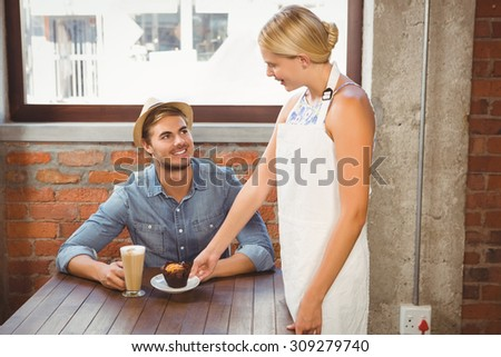 Smiling blonde waitress serving muffin to handsome hipster at coffee shop