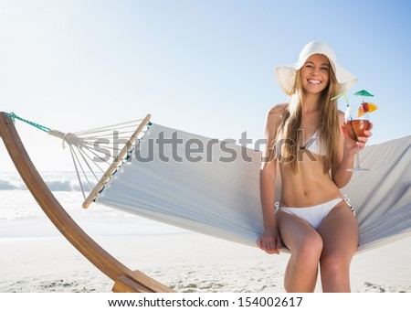 Smiling blonde wearing sunhat sitting on hammock with cocktail on the beach