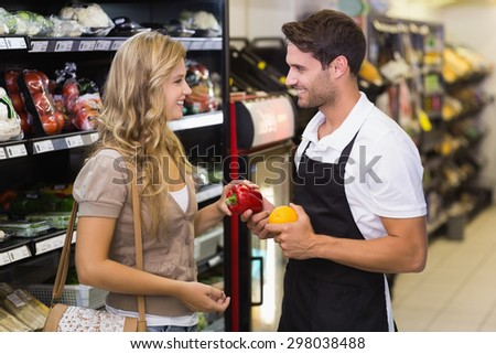 Smiling blonde woman buying a vegetables at supermarket