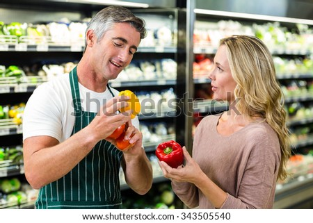 Smiling blonde woman buying a vegetables at supermarket - stock photo