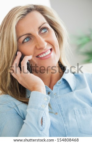 Smiling blonde woman calling someone with her mobile phone in a living room
