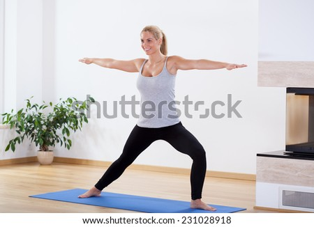 Smiling blonde woman during morning training at home