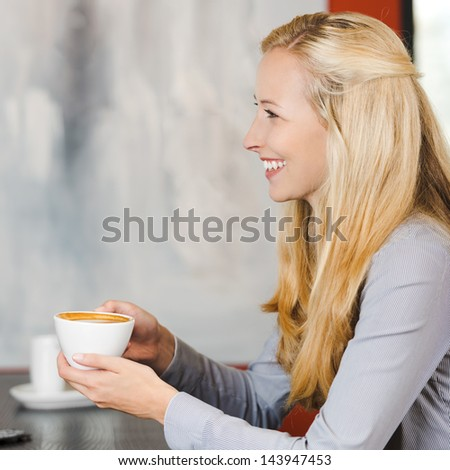 smiling blonde woman enjoying cappuccino at cafe