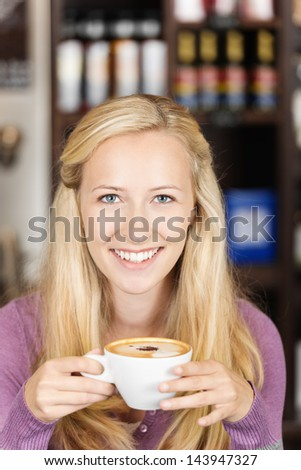 smiling blonde woman holding cup of cappuccino