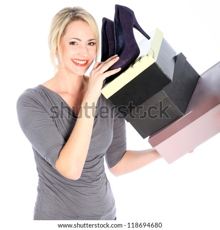 Smiling blonde woman holding high heels and shoe boxes on white background - stock photo