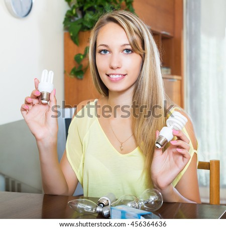 smiling blonde woman holding light bulbs stock photo edit now