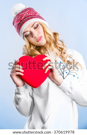 smiling blonde woman in a white sweatshirt holding a red heart. Valentine's day