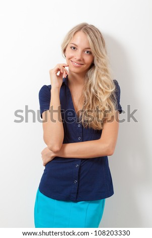 smiling blonde woman over white wall, looking at camera - stock photo