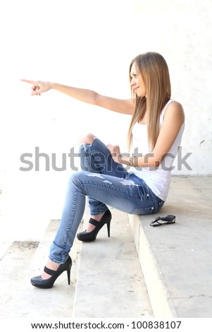 Smiling blonde woman pointing at someone