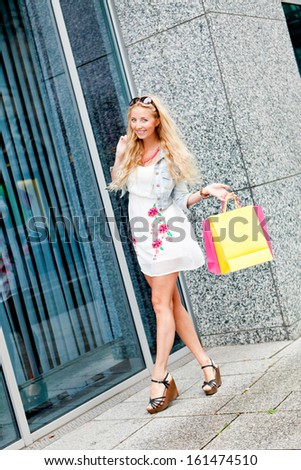 smiling blonde woman with colorful bags on shopping tour in the city outdoor