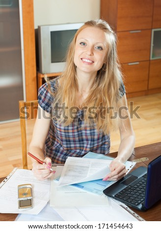 Smiling blonde woman with financial document and laptop at home