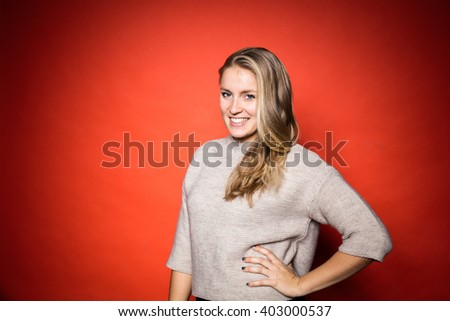 Smiling Blonde woman with grey wool jersey posing in front of orange background in studio with vibrant contrasty light