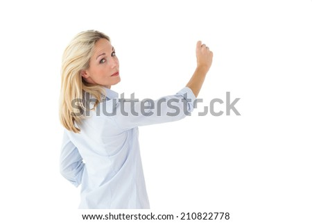 Smiling blonde woman writing and looking at camera on white background - stock photo