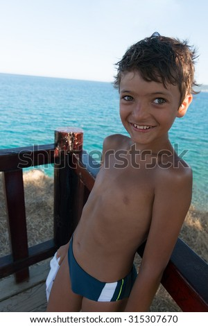 Smiling boy against a sea - stock photo