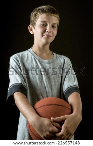 Smiling boy, age 11, holding basketball