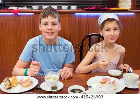 Smiling boy and girl have breakfast at table in small cafe.