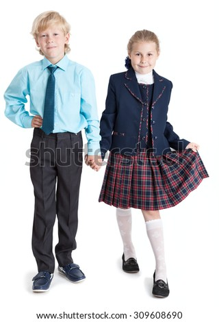 Smiling boy and girl in school uniform standing together holding hands, full length, isolated on white background - stock photo