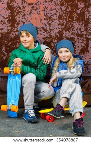 Smiling boy and girl with color plastic penny boards or skateboards outdoor