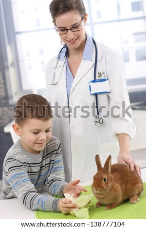Smiling boy and vet feeding pet rabbit with apple and lettuce at pets' clinic.
