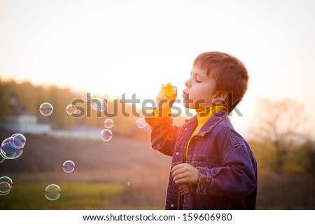 Smiling boy blowing the soap bubbles on the autumn landscape against sunset - stock photo