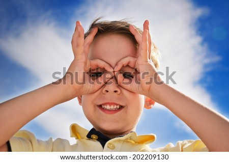 smiling boy did fingers like binoculars and looks through them. horizontal - stock photo