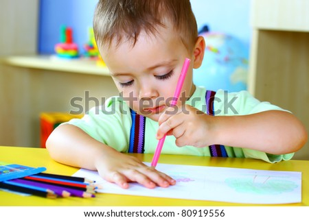Smiling boy draws with crayons