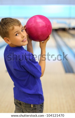 Smiling boy dressed in blue T-shirt holds pink ball in bowling club, stands with his back to camera and turns; shallow depth of field - stock photo