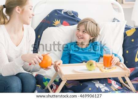 Smiling boy eating fruit and drinking juice in bed, on a bed tray, laughing with his mother