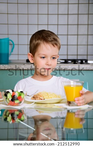 Smiling boy having dinner at the table and takes a glass of orange juice to drink. horizontal - stock photo