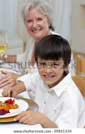 Smiling boy having dinner with his family at home - stock photo