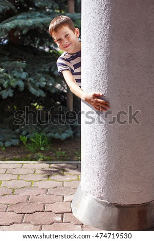 smiling boy hiding behind a pillar. play peekaboo. child playing hide and seek outdoors peeking from behind a pillar. looking at camera