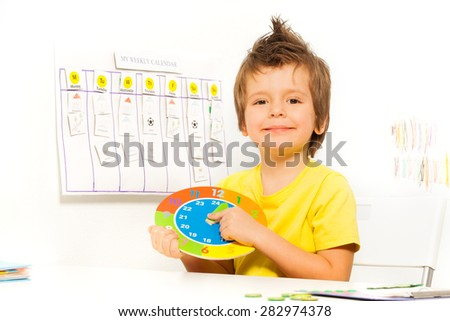 Smiling boy holding colorful carton clock sitting - stock photo