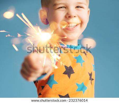Smiling boy holding fireworks - stock photo