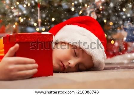 Smiling boy holding his present and sleeping under the christams tree  - stock photo