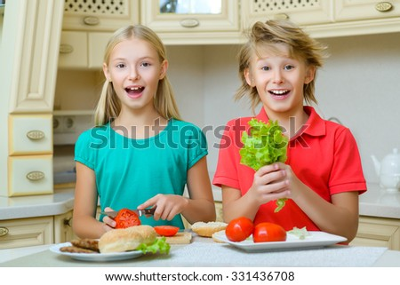 smiling boy holding salad standing next to girl who cuts the tomato in kitchen - stock photo