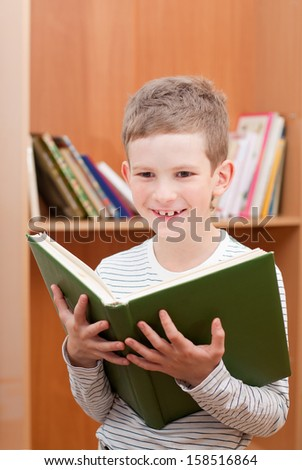 Smiling boy holds big green book - stock photo