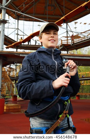 Smiling boy holds safety rope near Rope way on special playground - stock photo