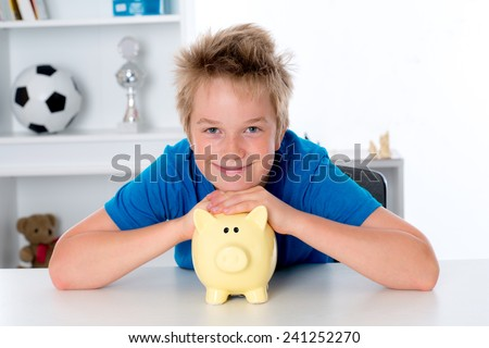 smiling boy in blue shirt with piggy-bank - stock photo