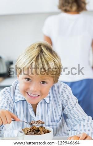 Smiling boy in kitchen having breakfast - stock photo