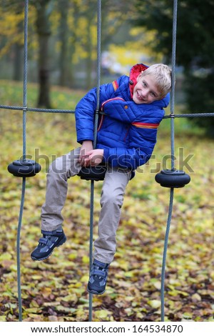 Smiling boy in warm blue coat having fun on the playground in the park on a sunny autumn day - stock photo