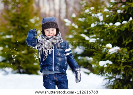 Smiling boy in warm winter clothes throwing snowballs in the winter forest - stock photo